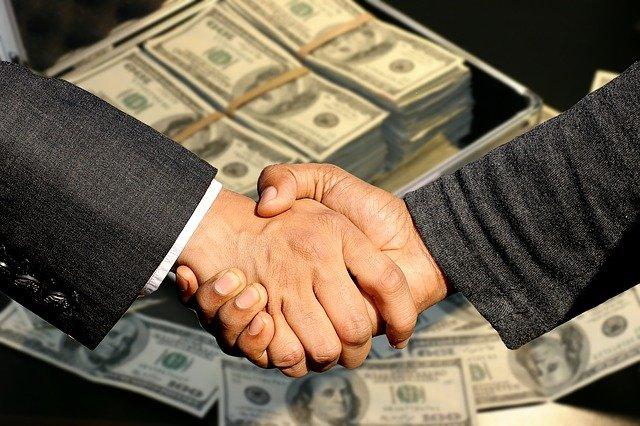 ruce před kufrem peněz